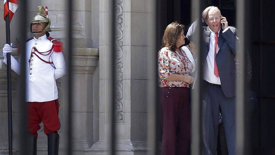 Peruvian President Pedro Pablo Kuczynski talks on his cellphone as he leaves the Government Palace in Lima on Wednesday.