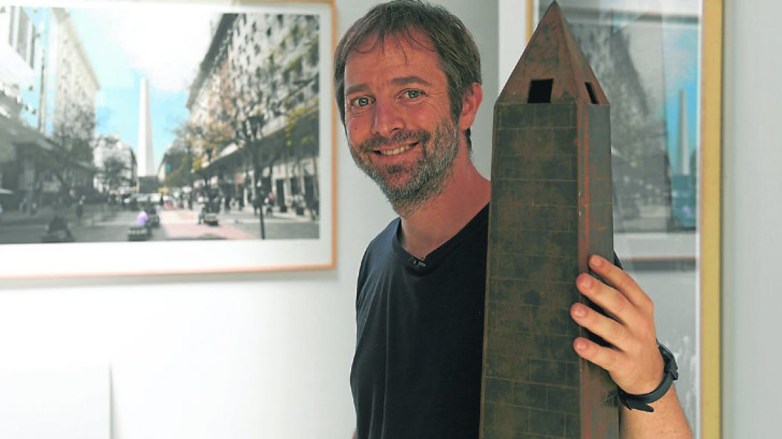 Leandro Erlich poses with a miniature reproduction of Buenos Aires' Obelisck, backdropped by a picture of his artwork La Democracia del Simbolo, 2015 at his studio in the capital.