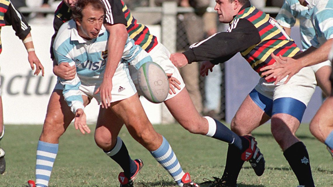 "In this file photo taken on April 17, 1999, former rugby player Hugo Porta (centre) from Argentina reaches for the ball as Berrie-Jon Mather tackles him, in Buenos Aires, during a friendly match between the Argentine ""Los Pumas"" and an international team of players. The event was held in celebration of the centenary of the Argentine Rugby Union."