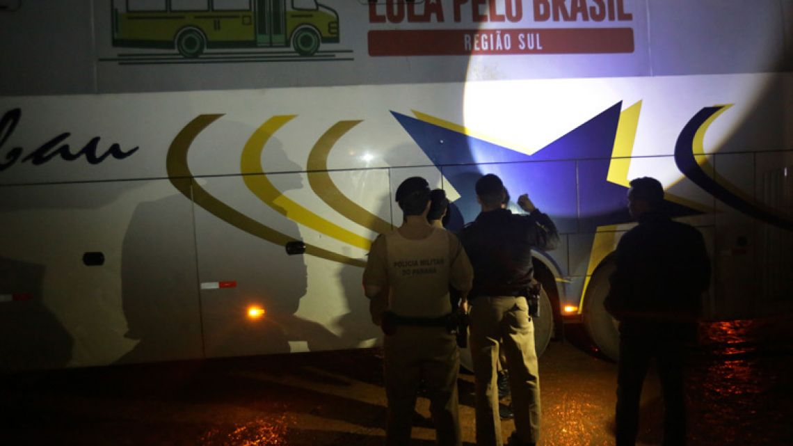 Police investigate a bus used by the campaign caravan carrying Brazil's former president Luiz Inácio Lula da Silva, at a parking lot in Laranjeiras do Sul, Paraná state. The Workers' Party says gunshots hit two buses in the caravan, but no one was hurt.