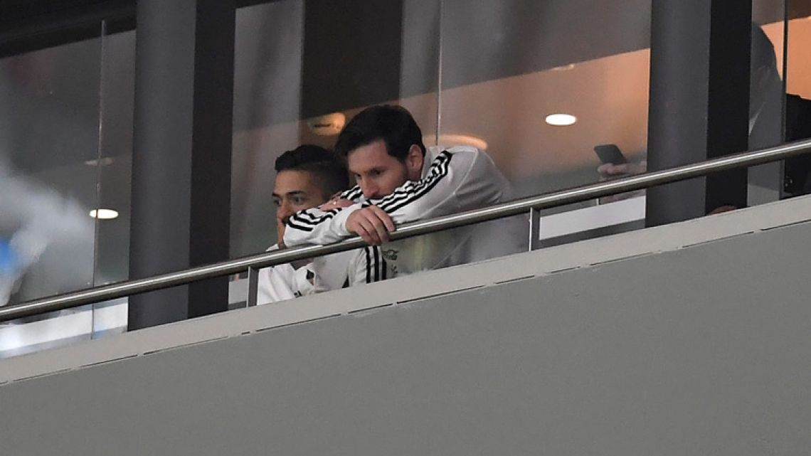 Lionel Messi, right, watches the international friendly match between Spain and Argentina at the Wanda Metropolitano stadium in Madrid last night. Argentina were thumped 6-1.