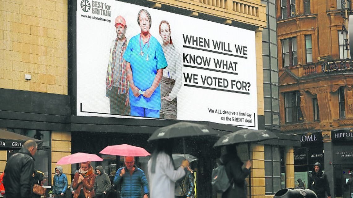 Pedestrians walk under a new billboard launched by campaign group Best for Britain, in Leicester Square in London.
