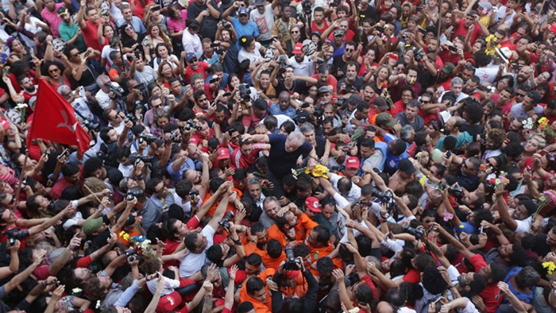 Handout picture released by Fotos Publicas shows Luiz Inácio Lula da Silva being lifted by supporters after attending a Catholic Mass in memory of his late wife Marisa Leticia Saturday.