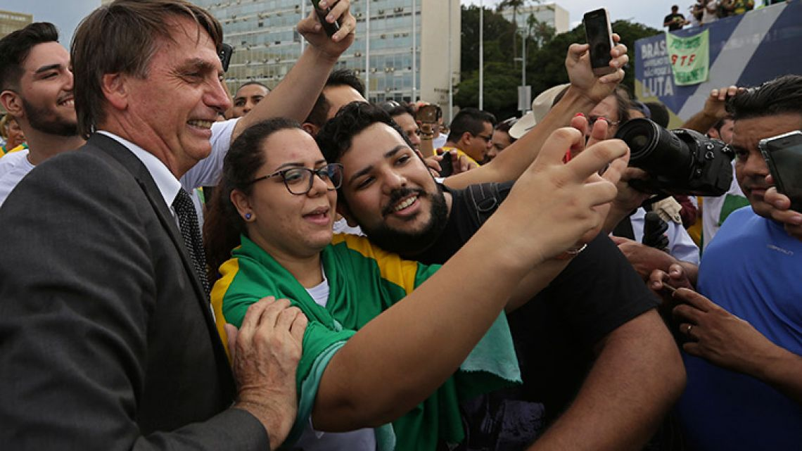 Demonstrators opposed to Brazil's former president Luiz Inácio Lula da Silva have their picture taken with far-right winger Jair Bolsonaro, the main right-wing candidate for the October presidential election, during a protest in Brasilia.