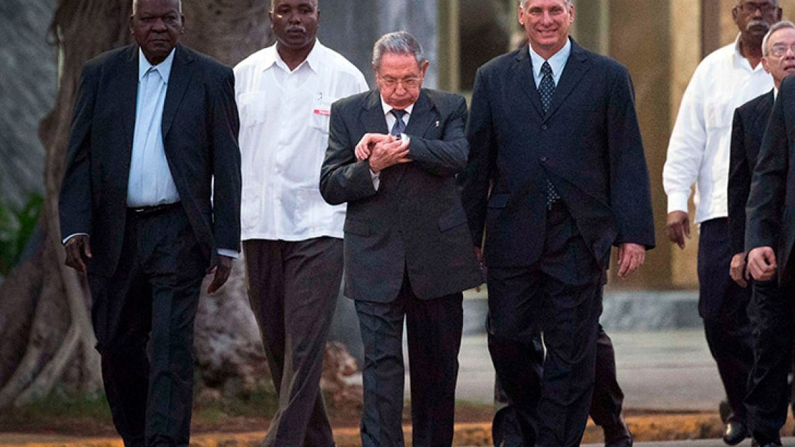 Cuba's President Raúl Castro looks at his watch as he walks with Cuba's Vice-President Miguel Díaz-Canel Bermúdez, right, and National Assembly of People's Power President Esteban Lazo Hernández, left, to the unveiling of a replica of a statue of Cuba's independence hero José Martí in Havana, Cuba.
