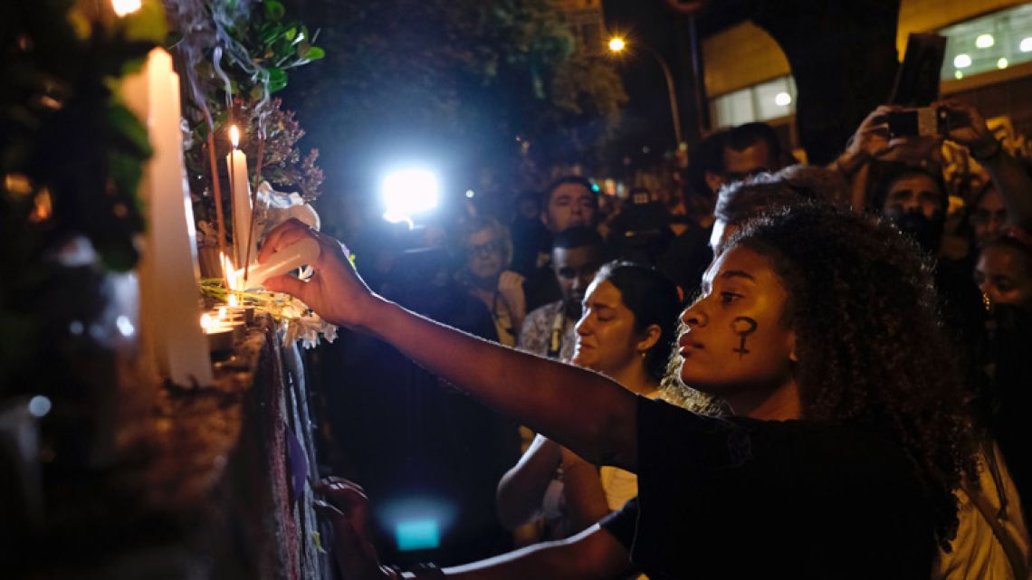 Candles are lit at a mural while mourning activist Marielle Franco in Rio de Janeiro on April 14, 2018, one month after her murder in Lapa. The murder of Franco, a black Brazilian activist who fought her way out of the slums to become a popular councilor, made headlines around the world. The outspoken 38-year-old, who was a critic of police brutality, an advocate for minorities and the posterchild of a new type of politics, was shot dead on March 14 in an assassination-style killing with four bullets to the head.