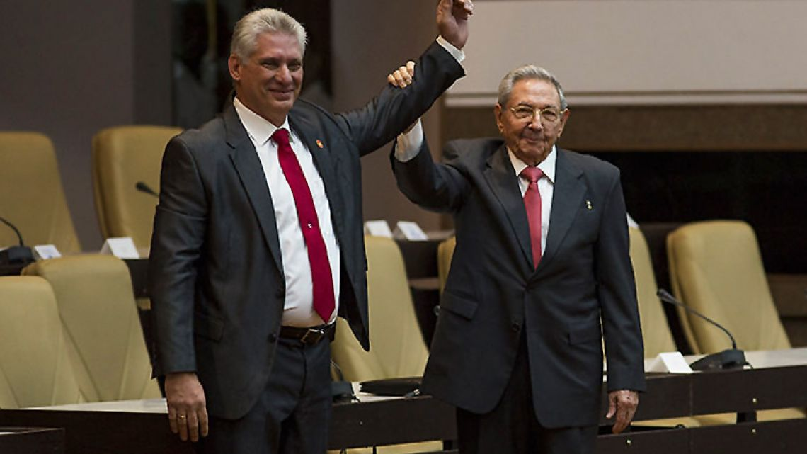 Handout picture shows outgoing Cuban president Raúl Castro (right) raising the arm of new President Miguel Díaz-Canel after he was formally named president by the National Assembly, in Havana.