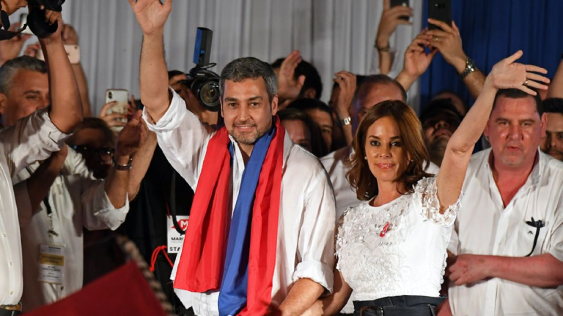 Paraguay's new President and presidential candidate of the Colorado Party, Mario Abdo Benítez, next to his wife Silvana López Moreira, wave to the crowd at Partido Colorado headquarters in Asuncion on April 22, 2018.