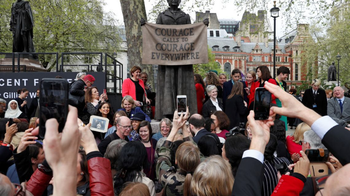 People pose for photographs with a statue of suffragist and women's rights campaigner Millicent Fawcett by British artist Gillian Wearing after it was unveiled in Parliament Square in London. The statue of women's rights campaigner Millicent Fawcett will stand alongside those of 11 men, including Britain's wartime leader Winston Churchill, Indian independence icon Mahatma Gandhi and anti-apartheid leader Nelson Mandela.