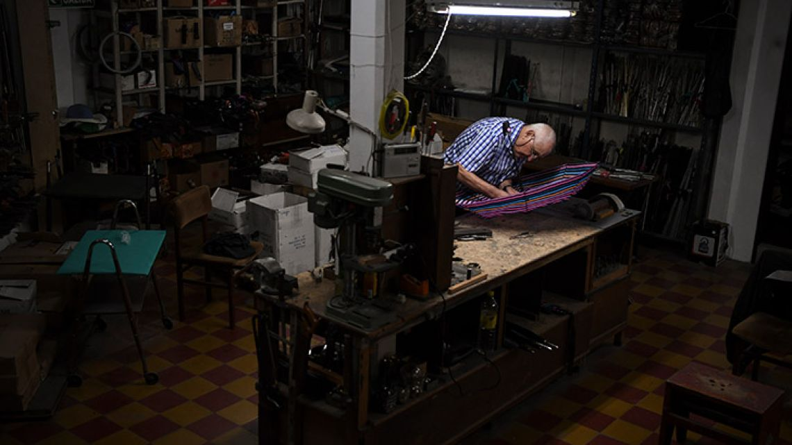 Umbrella fixer Elias Fernández, 87, works fixing umbrellas at his workshop in Buenos Aires.