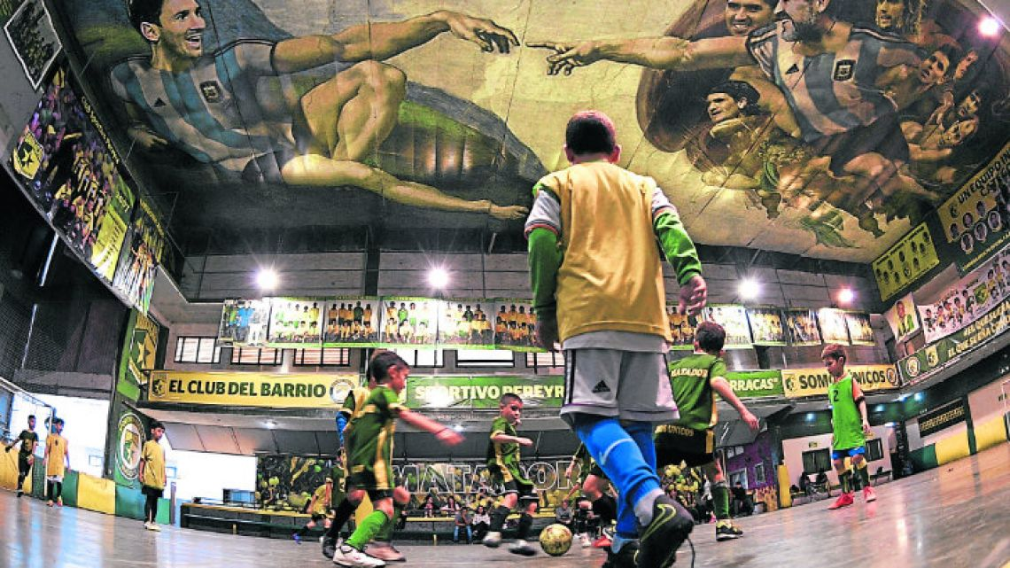 Children play football at Sportivo Pereyra de Barracas football club in Barracas, where local artist Santiago Barbeito created a football version of Michelangelo's Creation of Adam on the ceiling of the pitch. In the painting that represents the the long-lasting tradition of Argentine football, Adam is depicted by Lionel Messi, Diego Maradona stands for God, and the apostles are depicted by a number of other local legends of the game.