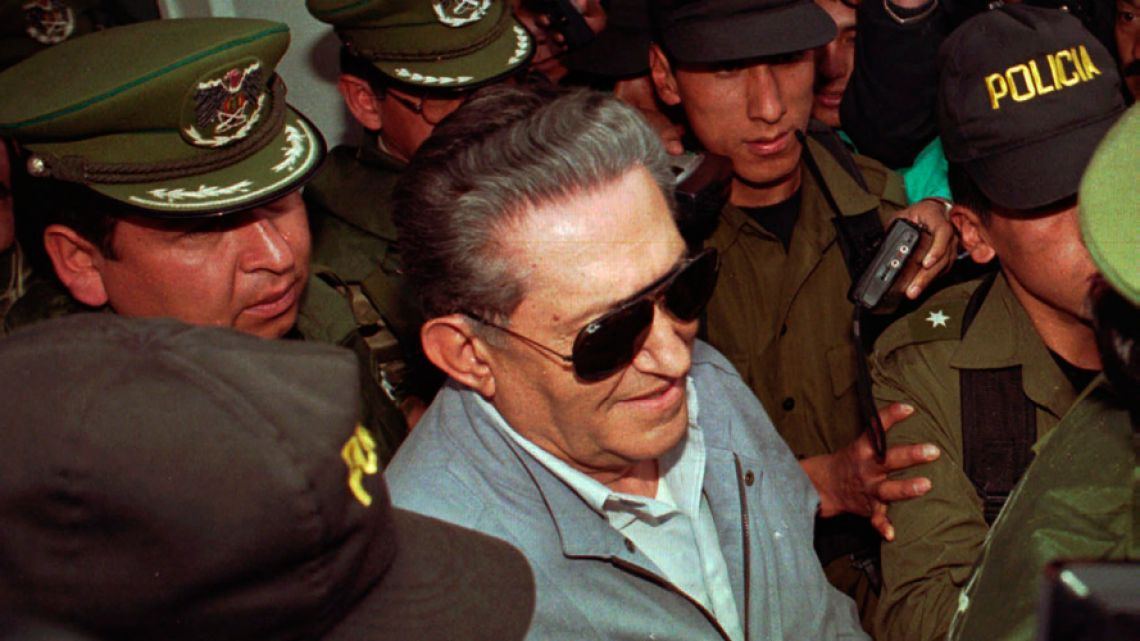 In this 1997 file photo, Bolivia's jailed, ex-dictator Luis García Meza is surrounded by police as he leaves the Copacabana clinic in La Paz, Bolivia.