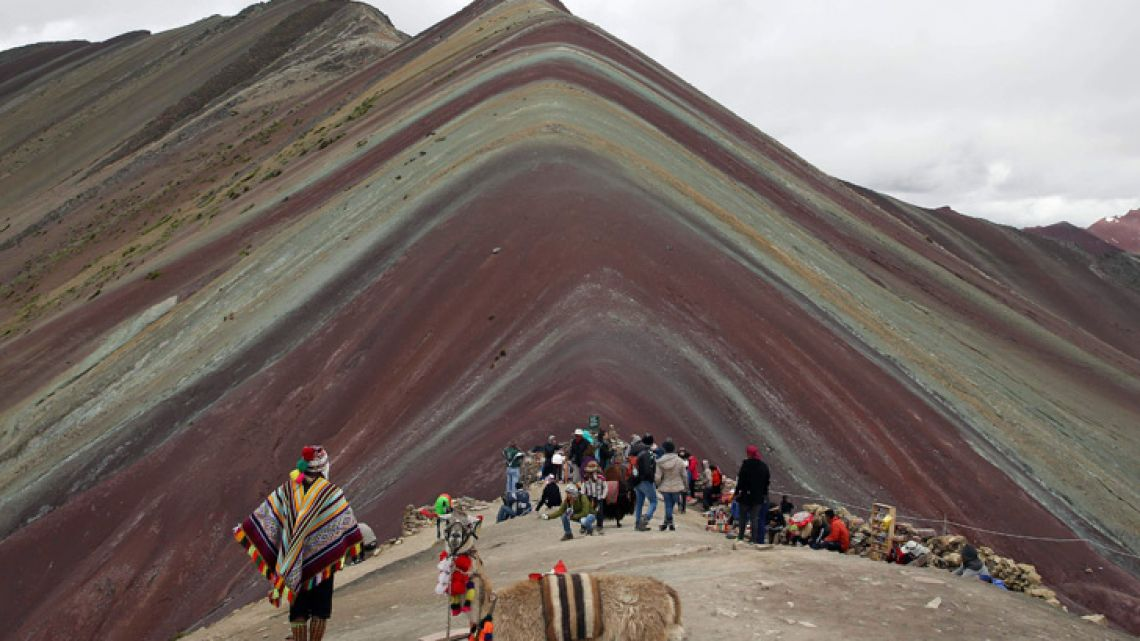 In this March 2, 2018 photo, an Andean man rests with his llama on 'Rainbow Mountain' in Pitumarca, Peru.