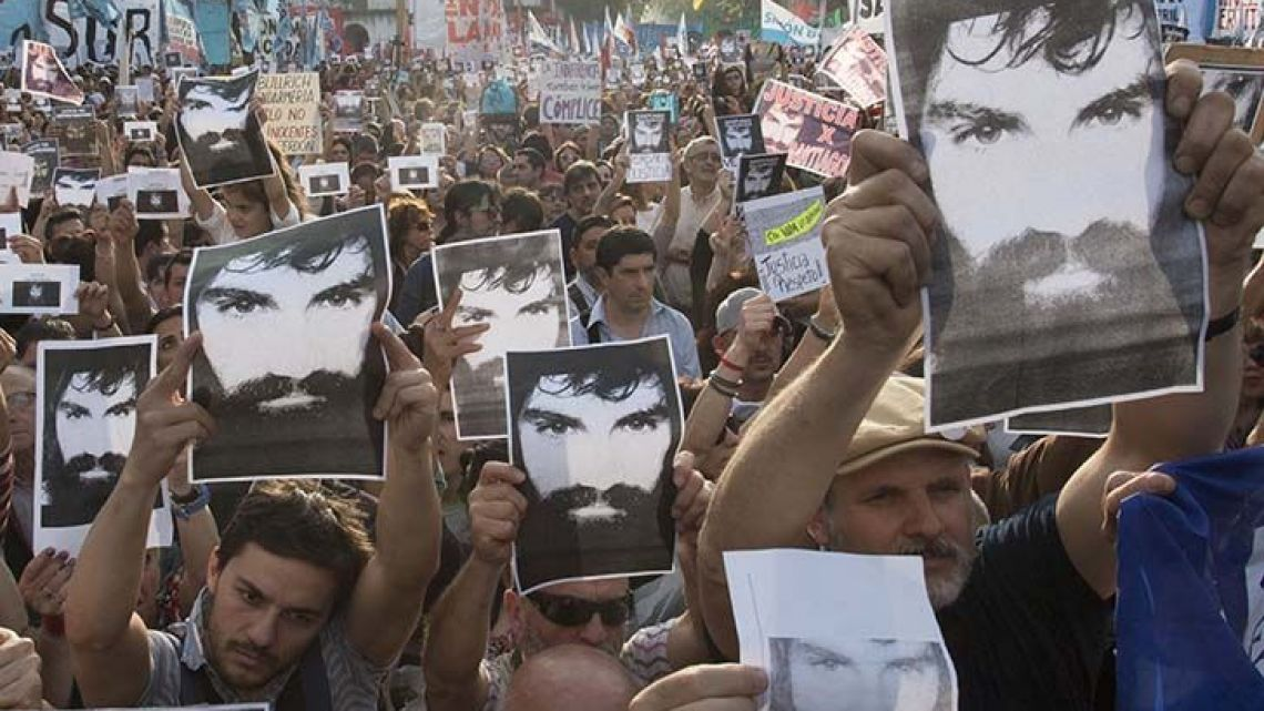 Protesters hold up an iconic photo of Santiago Maldonado during a rally.