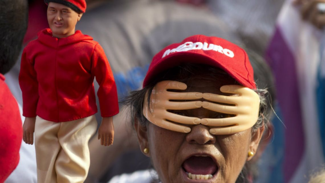 A woman wearing a set of hands over her face holds up a doll of Venezuela's late President Hugo Chavez during an election campaign rally for current President Nicolas Maduro.