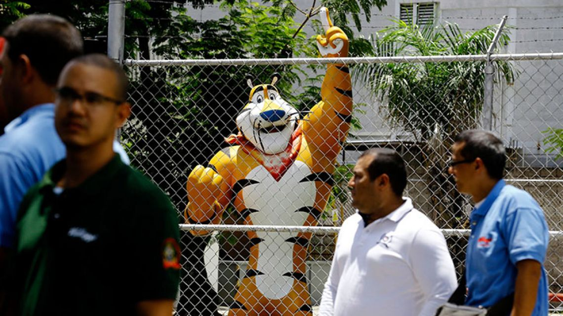 A statue of Kellogg's mascot, Tony the Tiger, stands behind the Kellogg's factory's fence, as workers gather outside in Maracay, Venezuela, Tuesday, May 15, 2018.