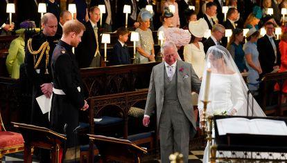 El príncipe Harry, duque de Sussex, mira a su novia, Meghan Markle, cuando llega acompañada por el príncipe Carlos de Gran Bretaña