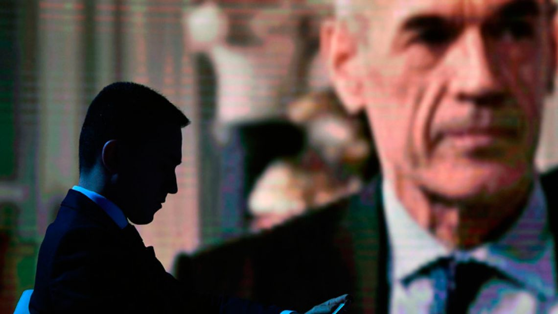 Five-Stars Movement leader Luigi Di Maio is silhouetted against a giant screen showing premier-designate Carlo Cottarelli during the Rai Uno TV program 'Porta a Porta' hosted by journalist Bruno Vespa, in Rome, Italy.