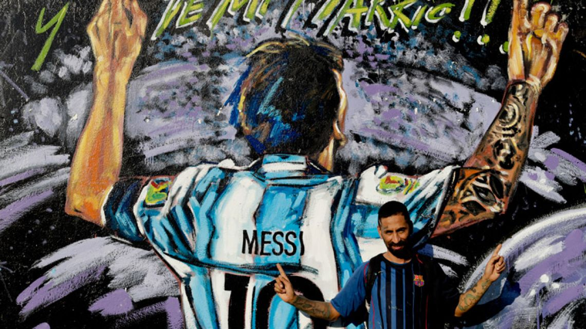 Alejandro Daniel Fernández poses for a photo by a mural of his childhood friend, Lionel Messi, in La Bajada, Rosario, Argentina. Fernandez said Messi's family had always helped him, including living with the family for a while, and that he remains friends with Lionel and his brother who all play soccer together when in town.
