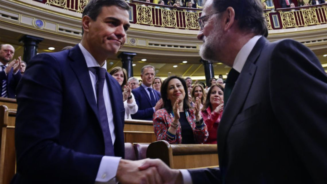 Rajoy shakes hands with PSOE leader Pedro Sánchez after the resolution.