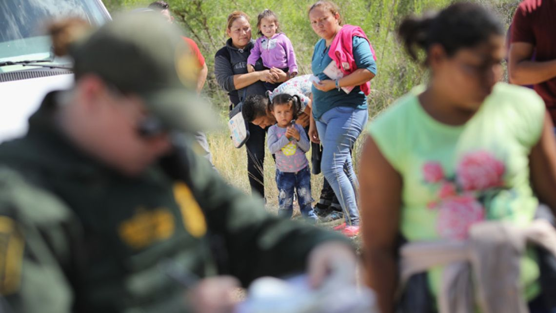 Central American asylum seekers wait as US Border Patrol agents take them into custody, on June 12, 2018 near McAllen, Texas.