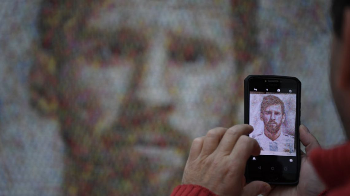 A person takes a picture of a mural of Lionel Messi, made with 2,000 football stickers being exhibited at the Casa Rosada Museum in Buenos Aires City.