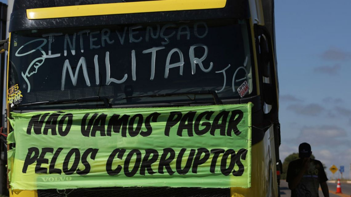 """A striking trucker protests rising fuel costs as he walks beside a truck with a sign that reads in Portuguese: """"We won't pay for the corrupt. Military Intervention now!"""""""