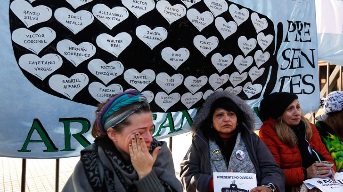 Lucia Zunda Meoqui, sister of Adrian Zunda Meoqui, left, an Argentine Navy officer onboard the ARA San Juan submarine that sank and disappeared on November 15, 2017, cries as she and others chain themselves to the fence of the Casa Rosada.