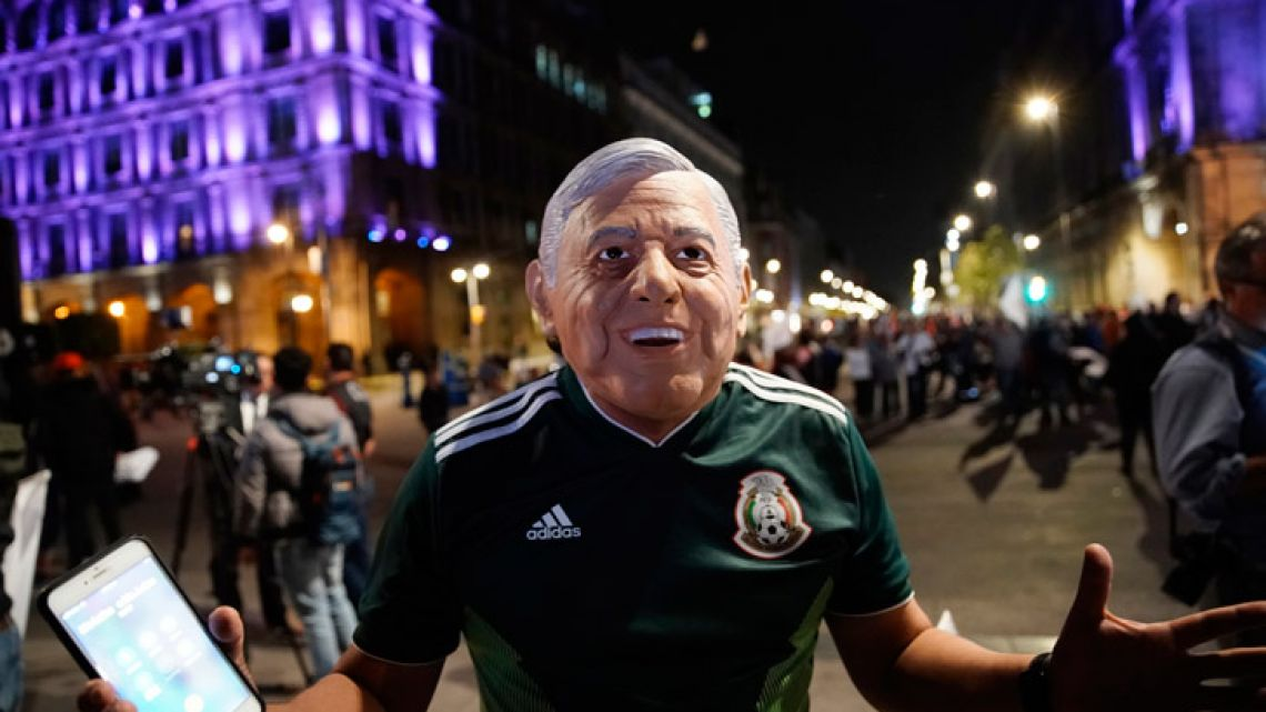 A supporter of presidential candidate Andrés Manuel López Obrador wearing a mask in the likeness of the candidate celebrates his victory, in Mexico City.