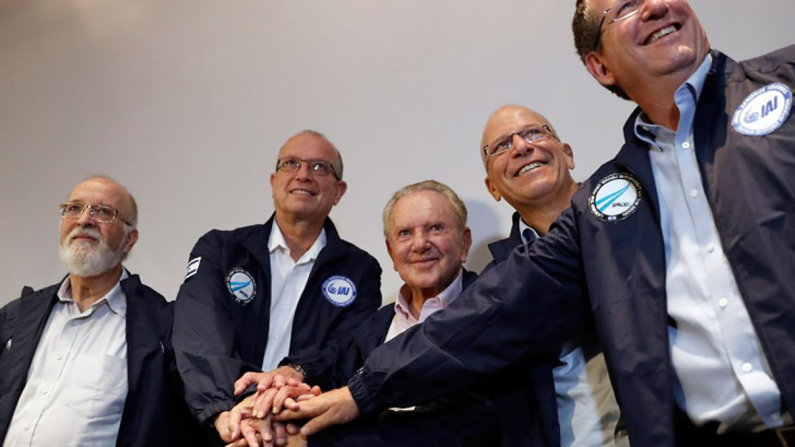 Israeli billionaire investor Morris Kahn (centre) poses with Israel Aerospace Industries (IAI) Space Division General Manager Opher Doron (first right), Space IL CEO Ido Anteby (second right), IAI's President and CEO Joseph Weiss, and chairman of the Israel Space Agency Itzhak Ben Israel (first left) during a press conference to announce the launch of a spacecraft to the moon, in Yehud, Eastern Tel Aviv, on July 10, 2018.