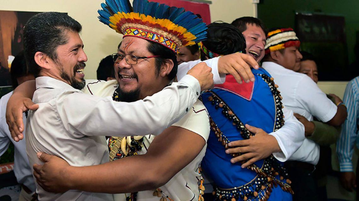 Pablo Fajardo (left), lawyer of the victims of enviromental damage caused during oil operations in the Ecuadorean Amazon from 1964 to 1990 blamed on Texaco, which Chevron acquired in 2001, celebrates with his clients, during a press conference in Quito on July 11.