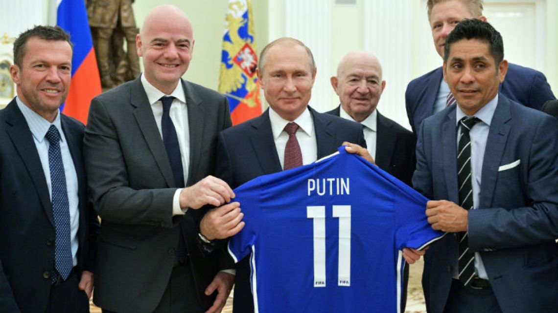 Putin holding his football shirt.
