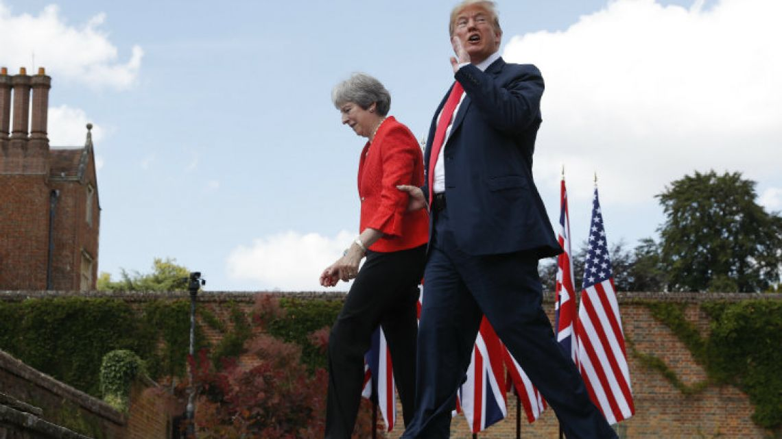 US President Donald Trump responds to a shouted questions as he walks with British Prime Minister Theresa May at the conclusion of their joint press conference at Chequers.