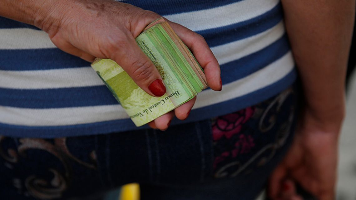 A woman holds a wad of bills to pay her bus fare in Caracas, Venezuela.