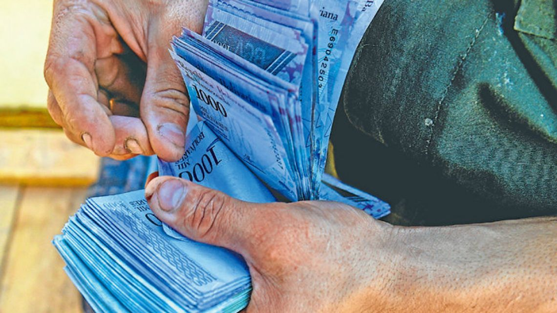 A man counts 1,000-bolívar-bills to buy groceries at the municipal market of Coche, a neighbourhood of Caracas.