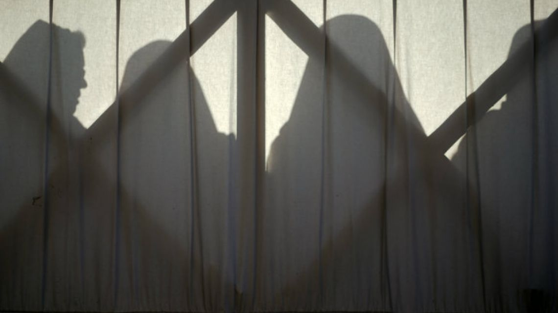 Nuns are silhouetted against a window in this photograph taken in St. Peter's Square at the Vatican.