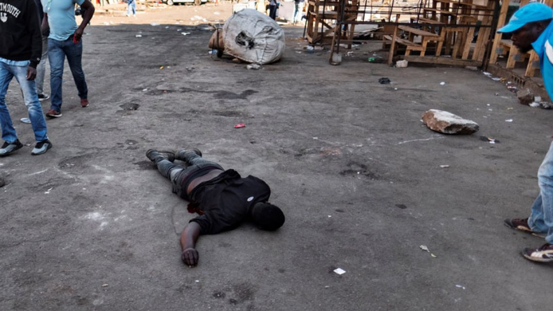 A man lies on the ground after the Zimbabwean army opened fire in central Harare on August 1, 2018 as protests erupted over alleged fraud in the country's election. The man died after being shot in the stomach, an AFP photographer said, confirming that he died at the scene. President Emmerson Mnangagwa on August 1 called for peace as police fired water cannon and teargas at opposition supporters in Harare over alleged fraud in Zimbabwe's elections.
