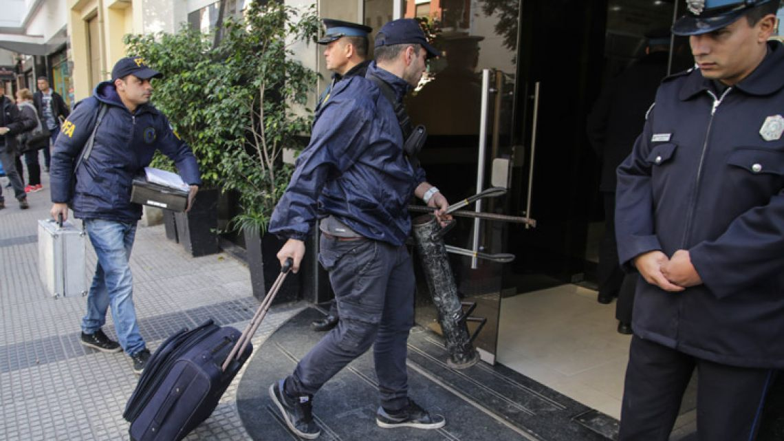 Police officers transport material confiscated during raids this morning across Buenos Aires City and Buenos Aires province, carried out as part of the investigation into an alleged corruption ring dating back to the Kirchnerite administrations.