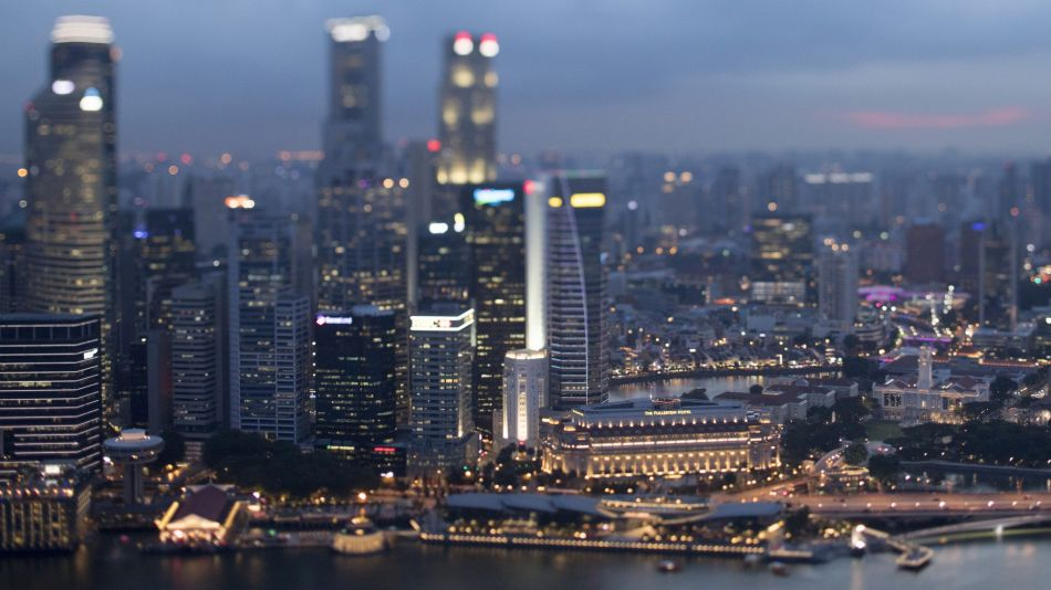 Commercial buildings standing in the central business district are illuminated at dusk in Singapore