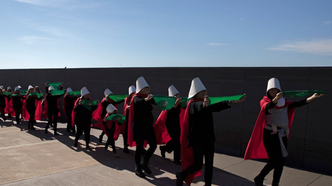 Activists in favour of the legalisation of abortion, dressed as characters from Canadian author Margaret Atwood's feminist dystopian novel 'The Handmaid's Tale,' display green headscarves as they perform at the Parque de la Memoria in Buenos Aires on Sunday.