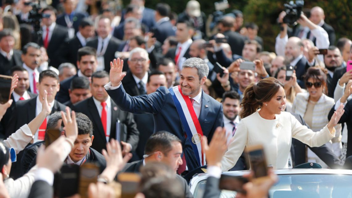 Paraguay's new President Mario Abdo Benitez rides in an open top car with his wife Silvana Lopez, after his inauguration ceremony in Asuncion on August 15, 2018.