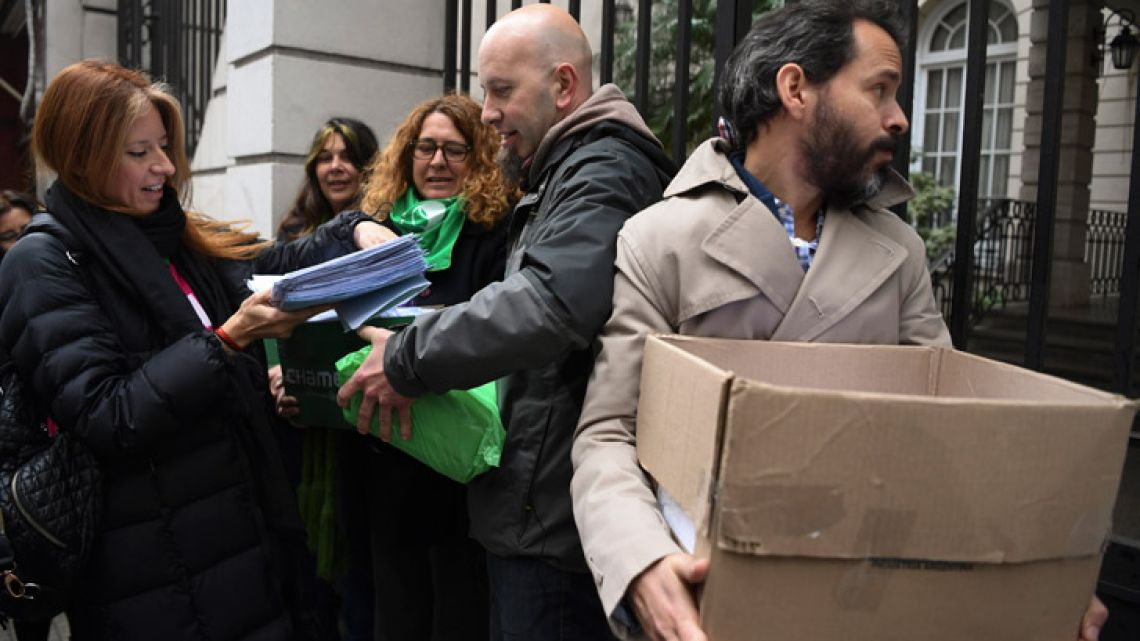 Activists prepare to deliver forms signed by people to renounce their religious affiliation to the Catholic Church outside the Argentine Episcopal Conference in Buenos Aires .