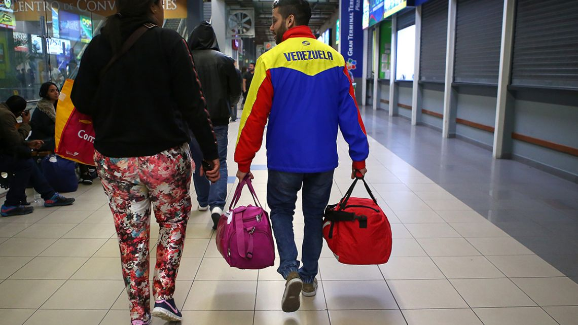 Venezuelan migrants walk at the bus terminal in the north of Lima, Peru, after arriving from a 20-hour trip.