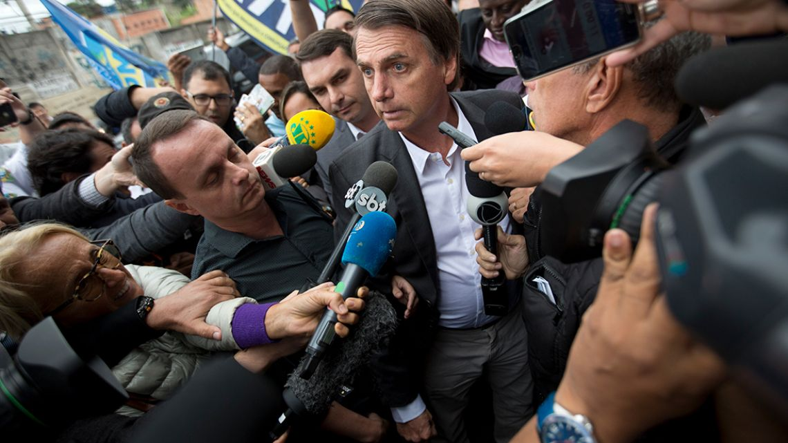 National Social Liberal Party presidential candidate Jair Bolsonaro talks to the press as arrives to campaign at the Madureira market in Rio de Janeiro, Brazil.