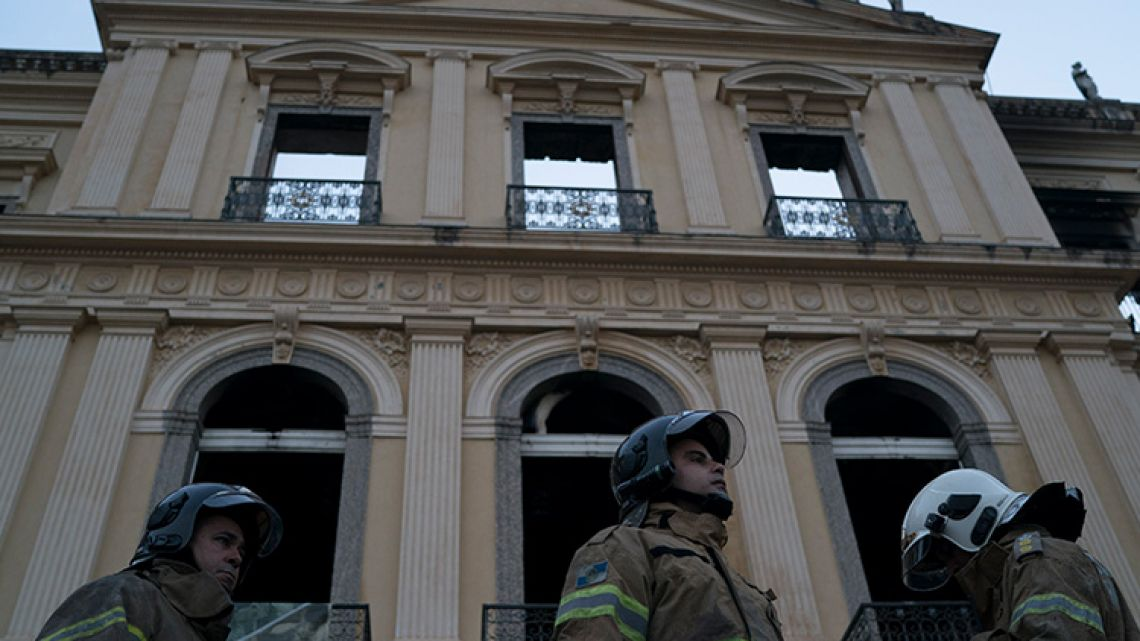 Firefighters stand in front of the destroyed National Museum of Rio de Janeiro.