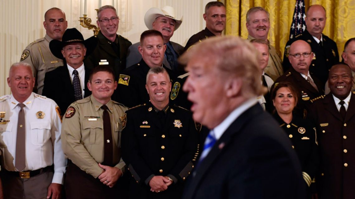 US President Donald Trump responds to a reporters question during an event with sheriffs in the East Room of the White House in Washington.