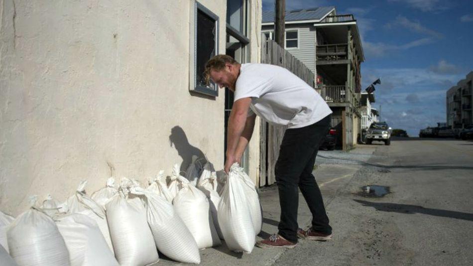 Un hombre apila bolsas de arena como defensa en su casa Wrightsville Beach, Carolina del Norte.