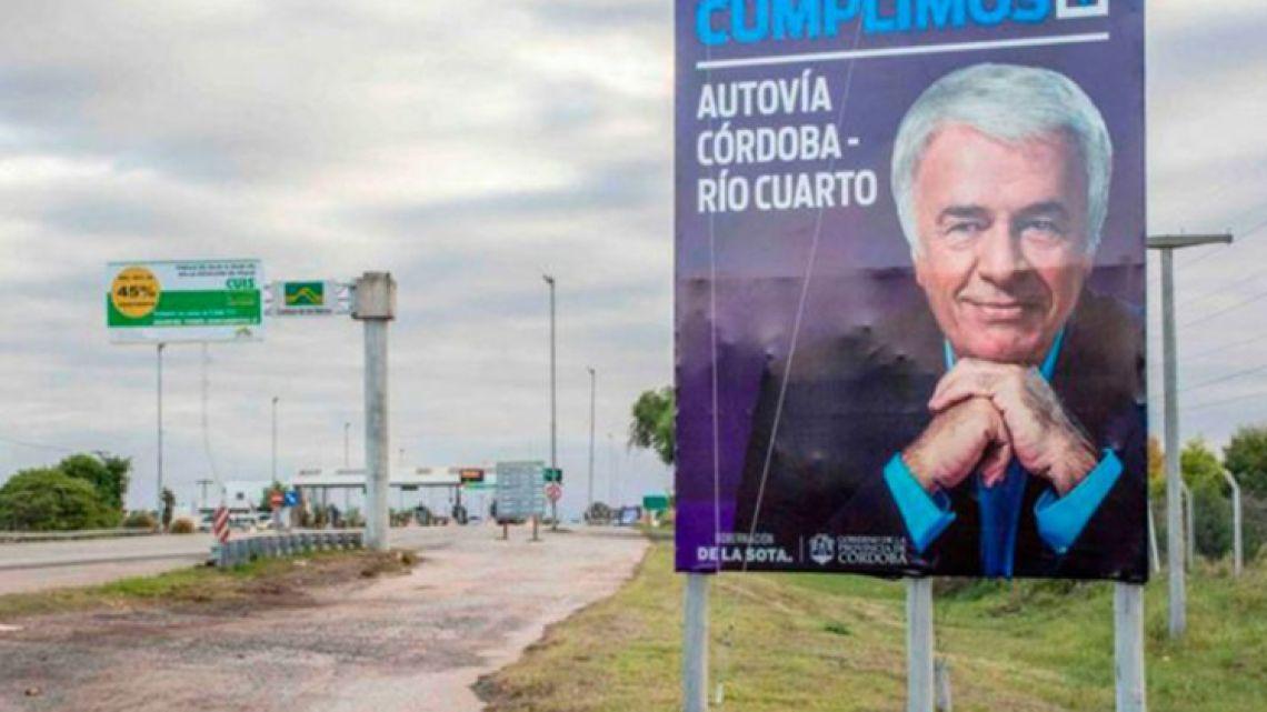 Former Córdoba governor José Manuel de la Sota seen on a sign celebrating his government's investment in roads.