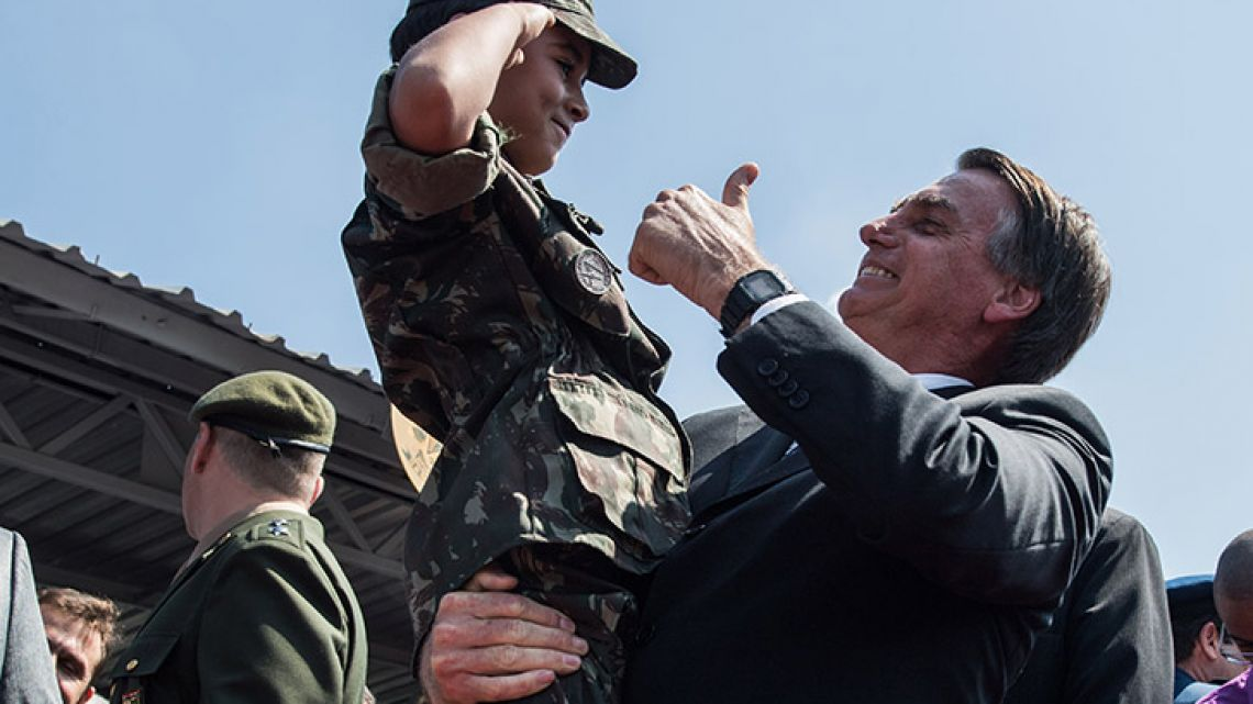 Presidential candidate, far-right congressman Jair Bolsonaro, holds a boy dressed in military uniform during a military event in São Paulo, Brazil. Less than a month before particularly uncertain elections in Brazil, military officers have rarely been so present in the political debate.