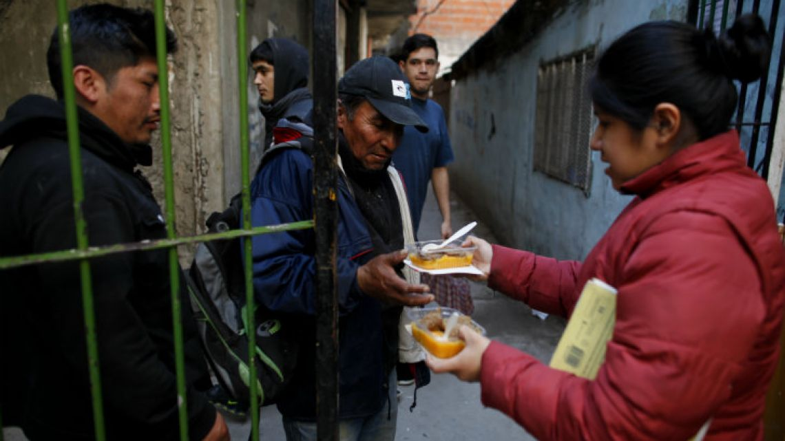 People line up for a small meal outside a soup kitchen at a community center in the Villa 1-11-14 shantytown on the outskirts of Buenos Aires.